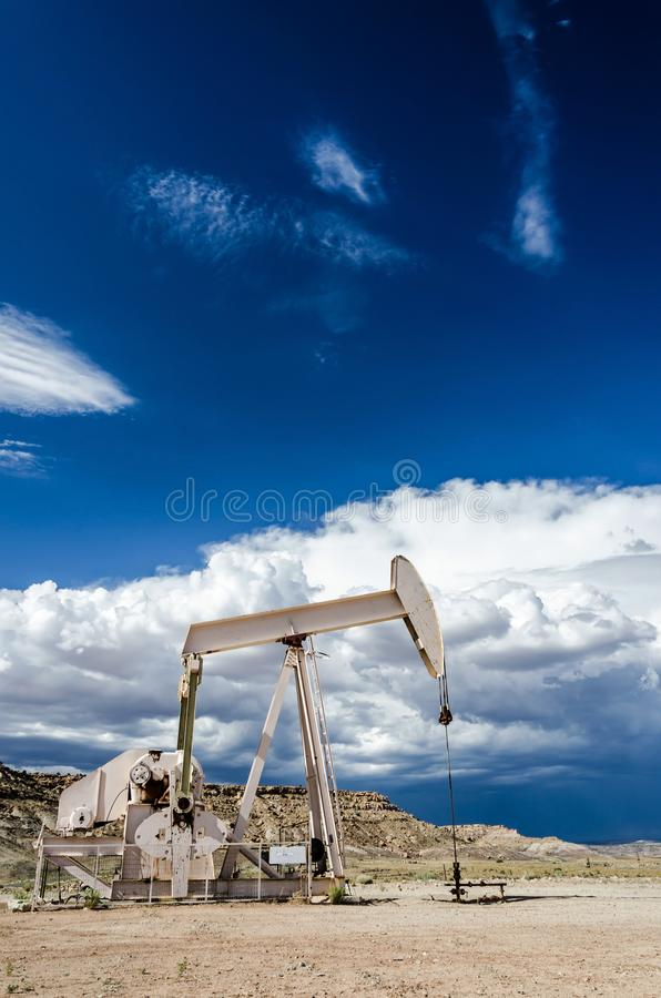 Oil pump in desert landscape with dark clouds in the background royalty free stock photos