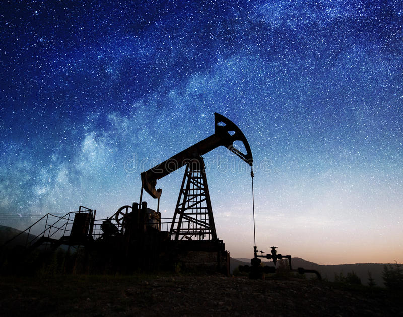 Oil pump on the oil field in the night. Silhouette of oil pump jack working on the oil field in the night under Milky way. Oil industry equipment stock image