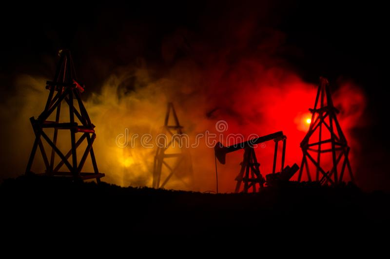 Oil pump oil rig energy industrial machine for petroleum, Group oil rigs and brightly lit industrial site at night. Toned.Backgrou. Nd for design. Selective royalty free stock photography