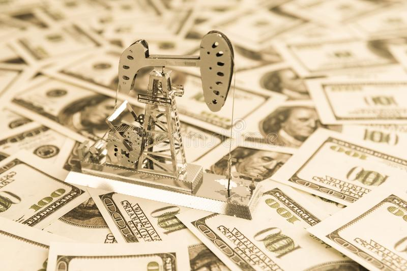 Fuel industry. oil business. Oil pump for oil production on the background of us dollar bills symbolizing high income from the sale of non-products royalty free stock images
