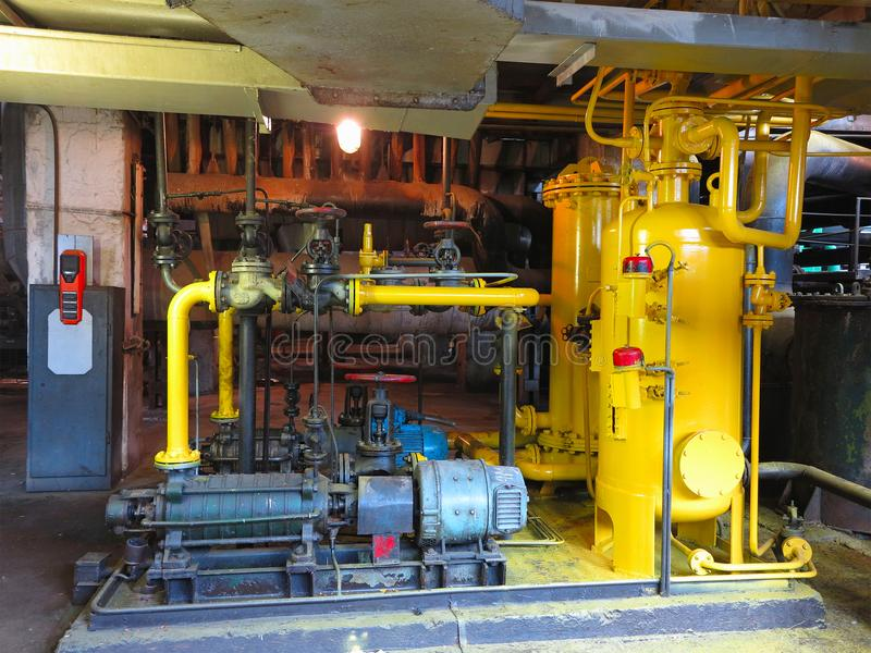 Oil pump, yellow pipes, tubes, machinery at power plant. Oil pump, yellow pipes, tubes, machinery at electric power plant stock image