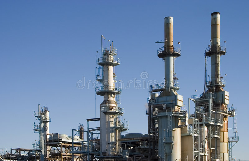 Oil Refinery 1. The complex arrangement of metal pipes and smoke stacks of a modern oil refinery royalty free stock photo
