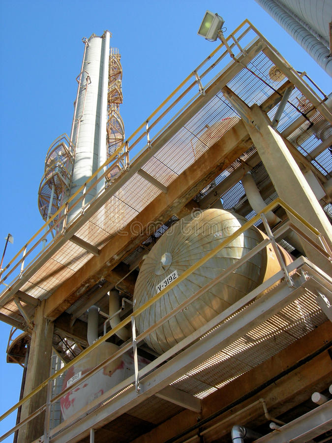 Oil Refinery. Exchangers and columns in an old oil refinery against a blue sky stock image