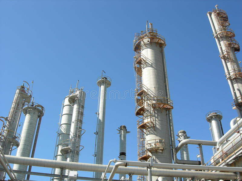 Oil Refinery. Distillation columns in an old oil refinery against a blue sky stock image