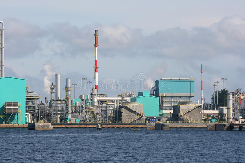 Oil Refinery. An oil refinery on the coast. This industrial looking building is located near a port. There is some gas being released stock photo