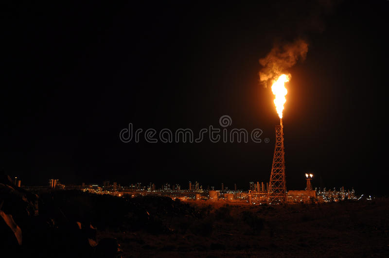Oil refinery. Burning flame at oil refinery in nighttime royalty free stock photo