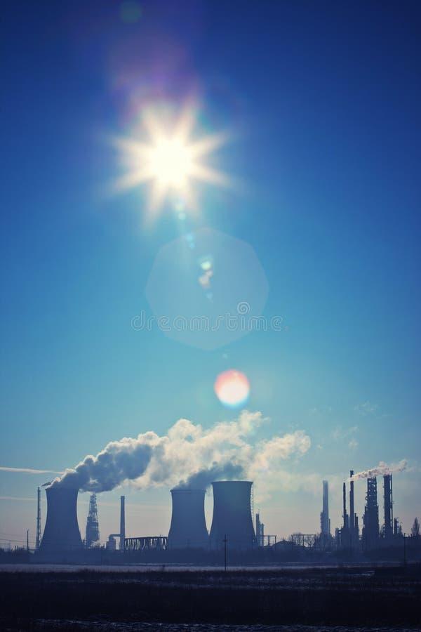 Oil refinery. Evacuation towers with smoke, sun shining creating flare royalty free stock image