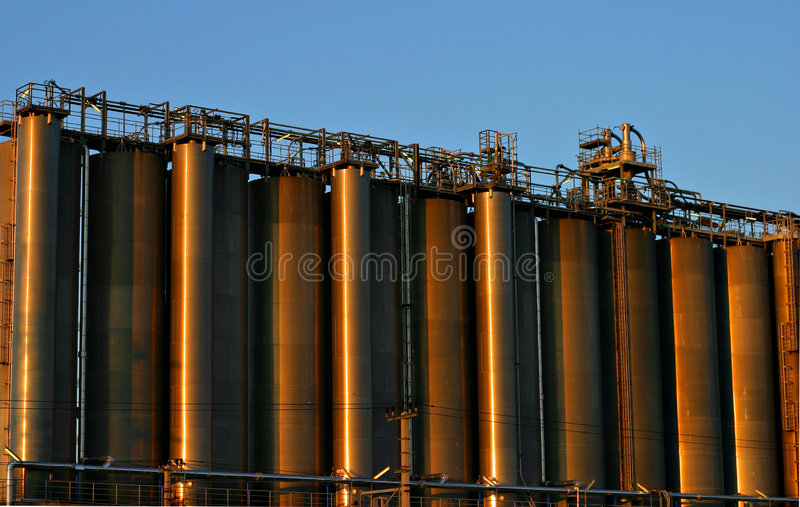 Oil refinery. Red / brown colored distillation colons in a crude oil refinery with a blue sky in the background stock images