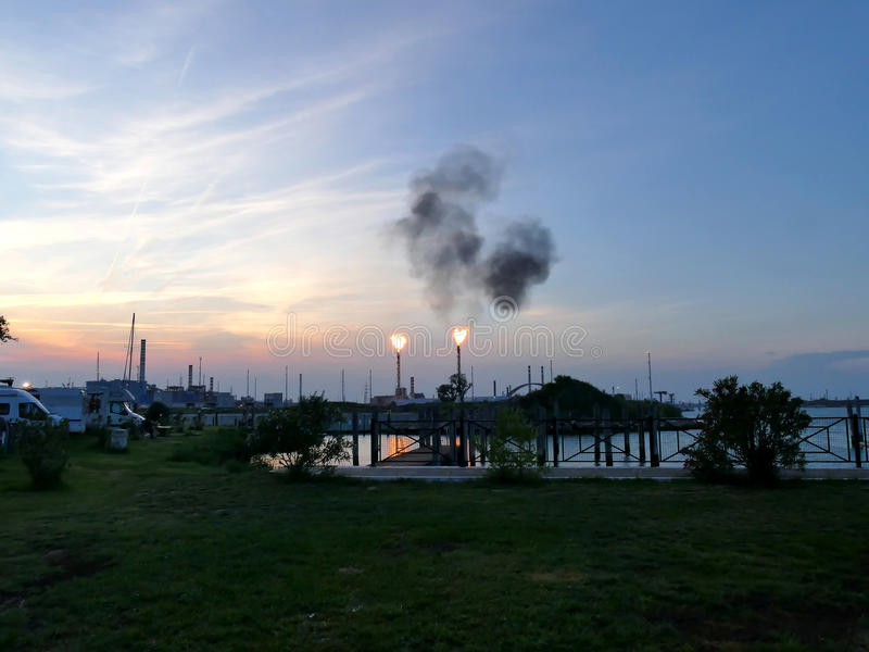 Oil refinery bursting flames at sunset close to camping site, Venice Italy. Oil refinery bursting flames at sunset, Venice Italy. Motor Homes on camping site royalty free stock images