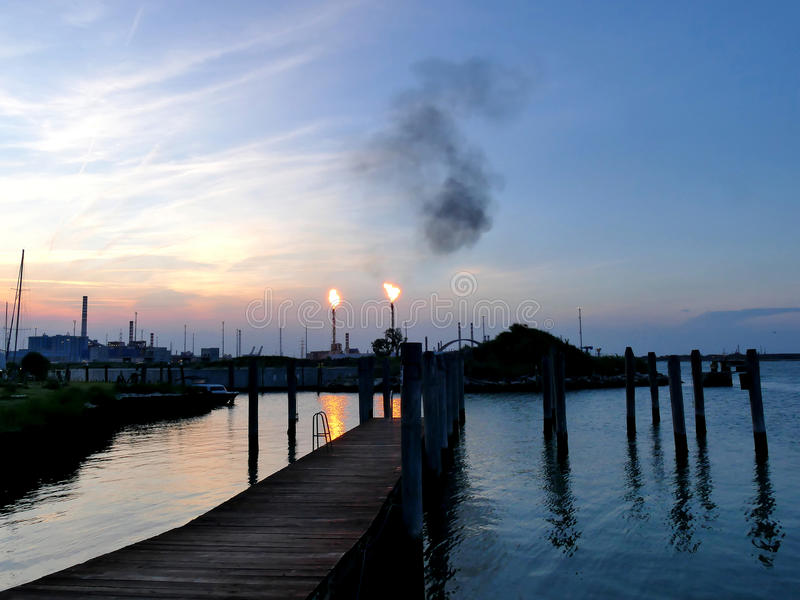 Oil refinery bursting flames at sunset, Venice Italy. Oil refinery bursting flames at sunset close to shore, Venice Italy stock photo