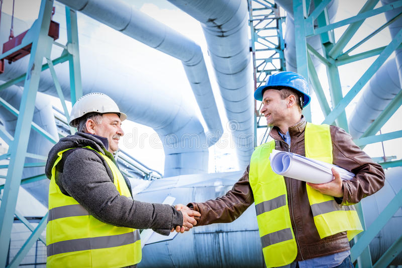 Oil refinery engineers successful deal handshake. Oil refinery engineers handshake. Petrochemical and gas industry successful deal. Cooperation concept stock photos