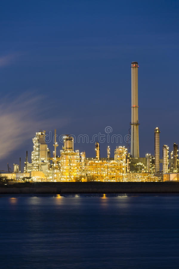 Oil Refinery In Harbor At Night. View over the Scheldt river to a large oil refinery with night blue sky, illumination and steam royalty free stock photo