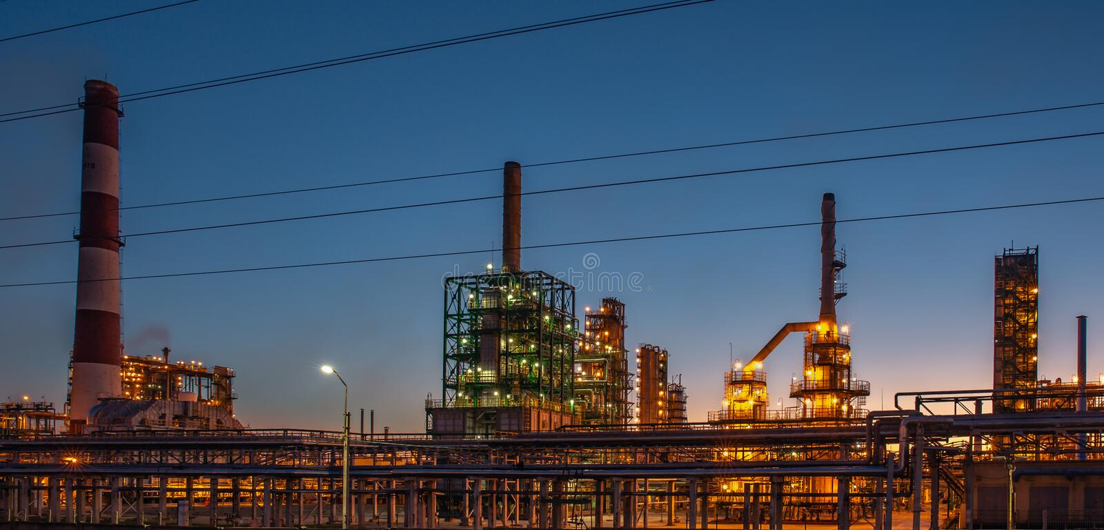 Oil refinery industrial plant or factory at sunset, storage distillery tanks and steel pipeline, modern petrochemical technologies. Toned royalty free stock images