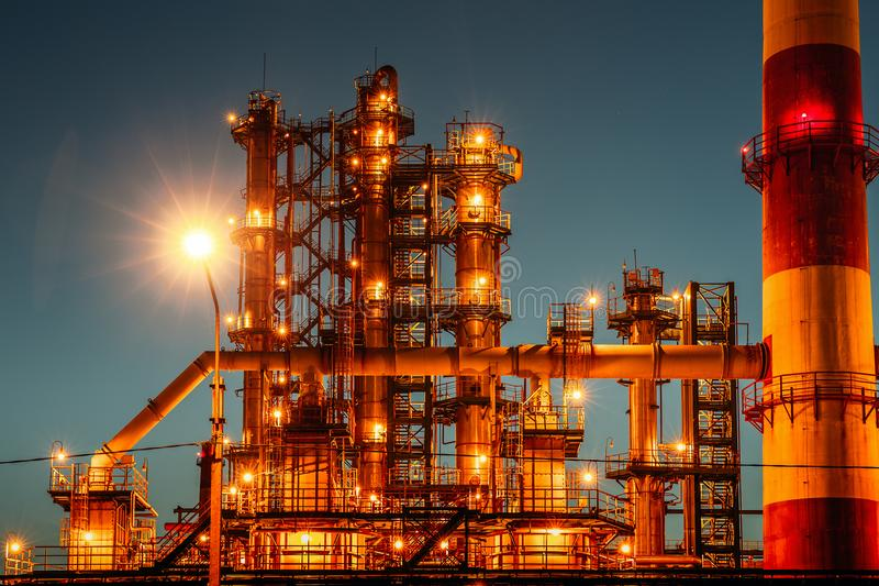Oil refinery industrial plant or factory at sunset, storage distillery tanks and steel pipeline, modern petrochemical technologies. Toned royalty free stock image