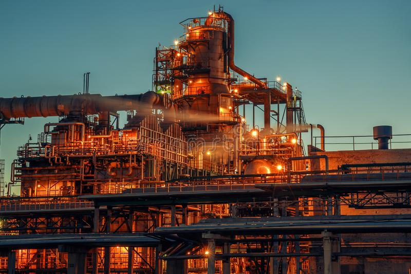 Oil refinery industrial plant or factory at sunset, storage distillery tanks and steel pipeline, modern petrochemical technologies. Toned stock photos