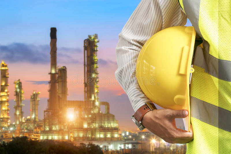 Oil refinery industry. Helmet engineers for security, standing with the details of stainless steel cylinder linings for the food industry royalty free stock photos