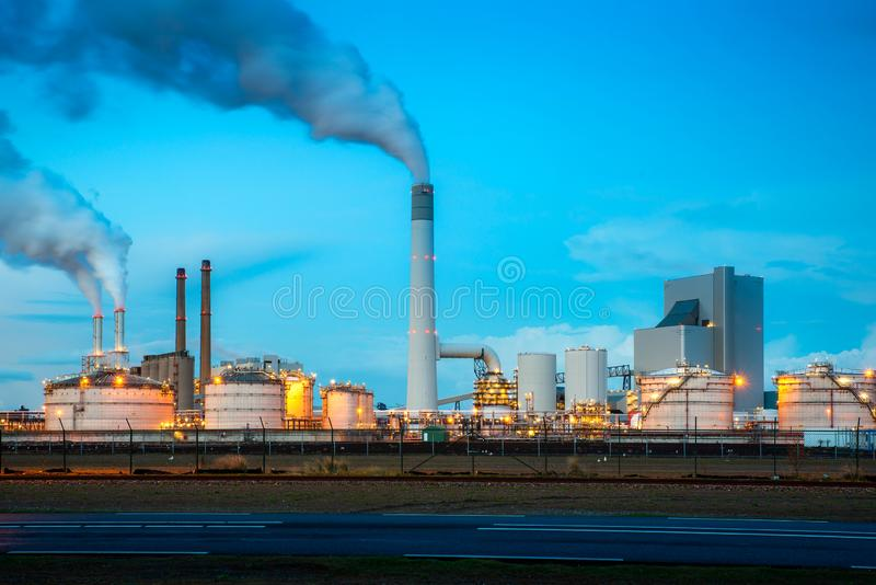 Oil refinery industry at night in Rotterdam, Netherlands. Pollution smoke from oil refinery industry use for environment industry royalty free stock photography