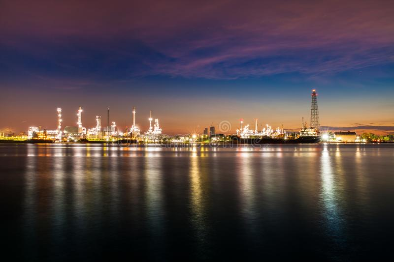 Oil refinery industry reflection on water at early morning under colorful sky of sunrise stock image