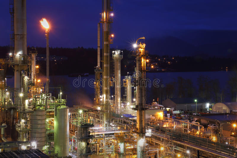 Oil Refinery Night Shift Energy. An oil refinery on the shore of Burrard Inlet working through the night. British Columbia, Canada near Vancouver royalty free stock image