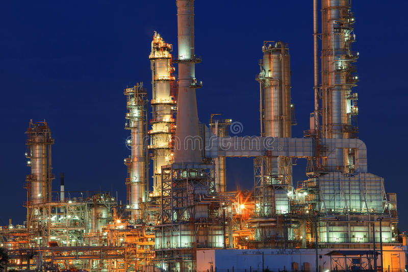 Oil refinery plant in petrochemical industry estate at night tim. E with blue sky background royalty free stock photo