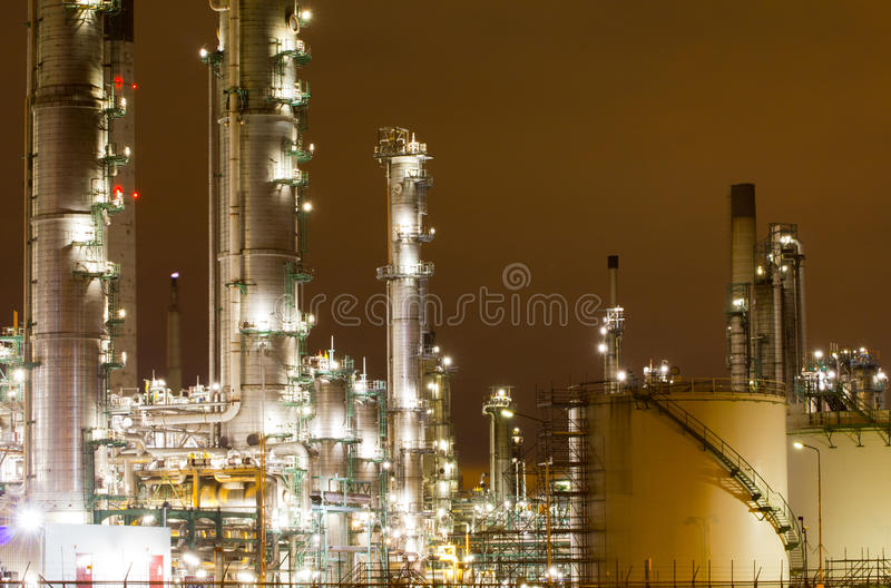 Oil-refinery plant. Storage tanks and chimneys of a large oil-refinery plant at night royalty free stock photo