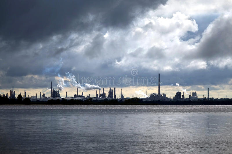 Oil refinery Processing Plant and Storm Clouds Sky. Crude oil and petroleum refinery industrial processing plant with smoke stacks spewing steam into a stormy stock images
