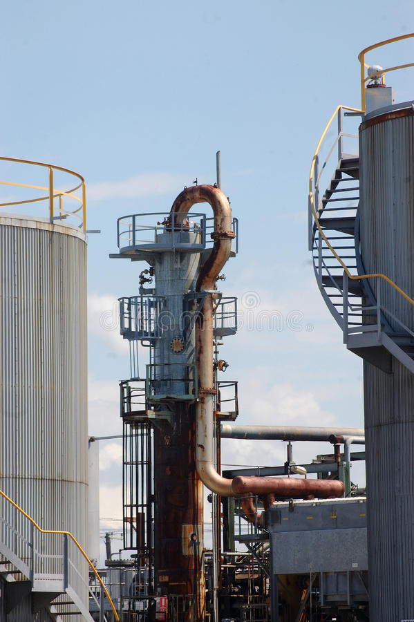 Oil refinery. Refractory tower for bitumen and tanks at oil refinery stock image