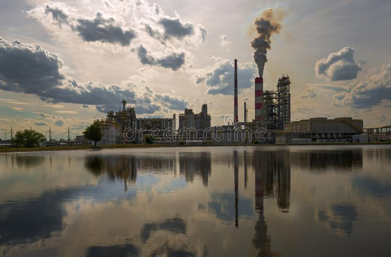 Oil refinery. The smoke from the chimney of oil refinery stock images
