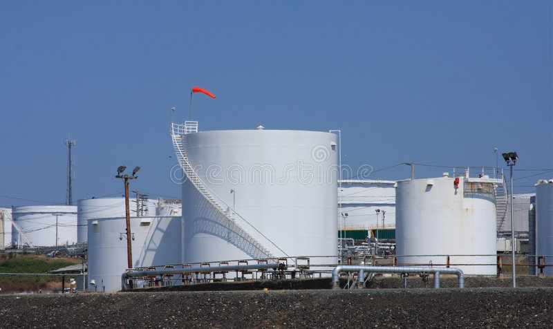 Oil Refinery Storage Tank. Several storage tanks at an oil refinery. Blue sky and a windsock above royalty free stock images