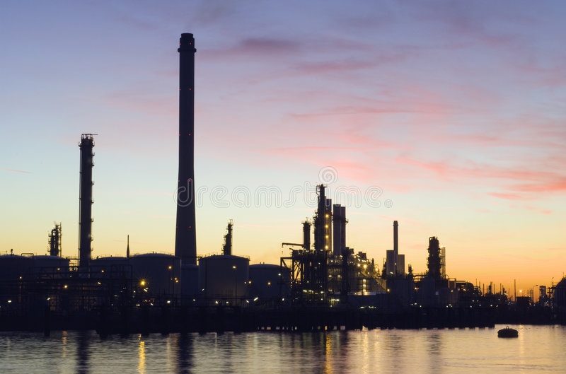 Oil Refinery at sunset. The silhouette of an oil refinery at sunset, against a radiant sky royalty free stock image