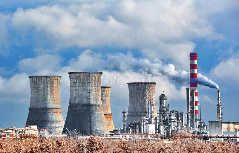 Oil refinery. View of oil petrochemical refinery with cloudy sky near town stock image