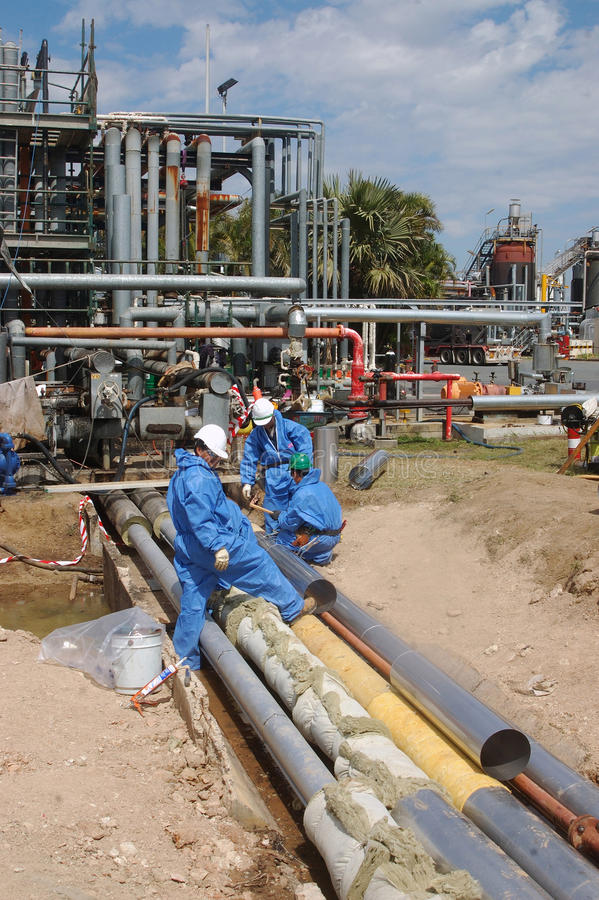 Oil refinery workers. Workers lag pipes at the BP oil refinery near the mouth of the Brisbane River, September 28, 2008, Brisbane, Australia stock image
