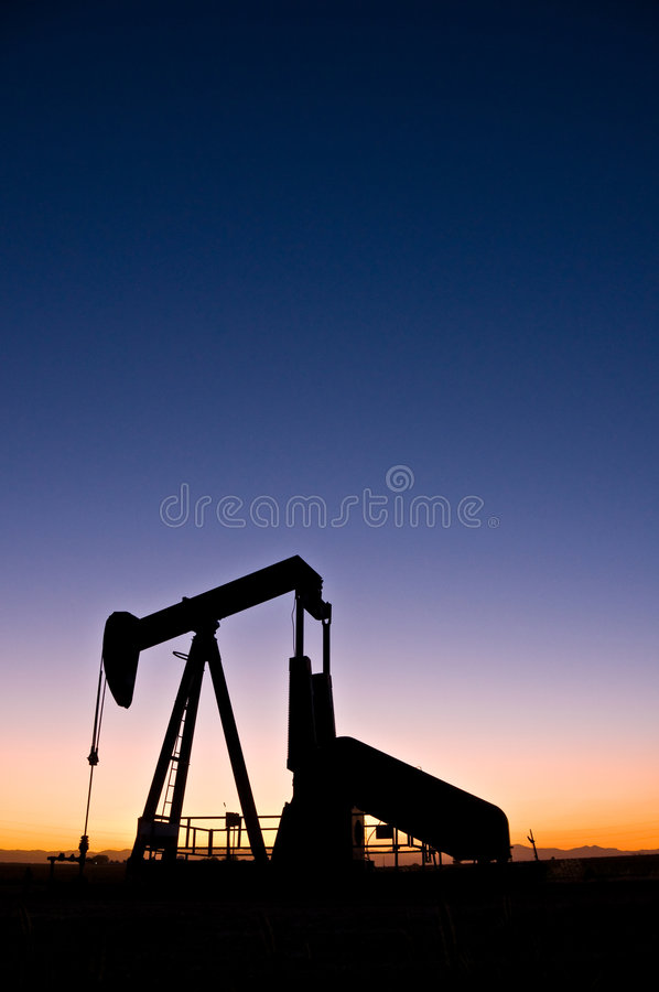 Oil Rig. A view of the machinery silhouette at an oil rig, at sunset