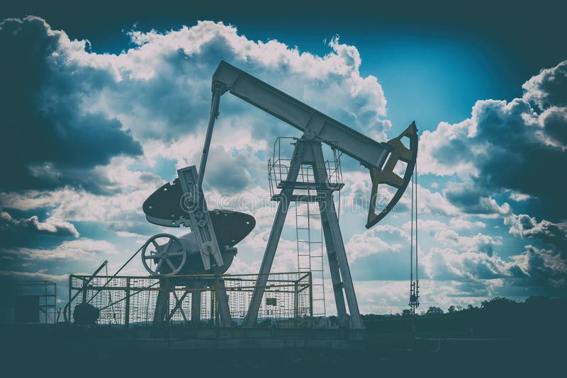 Oil rig on the background of the cloudy sky, dark retro toning stock image