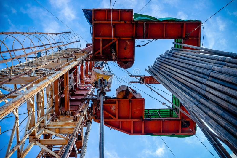Oil rig derrick in oilfield against the bright blue sky. Drilling rig in oil field for drilled into subsurface in order royalty free stock photo