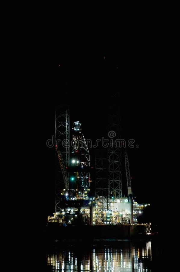 Oil rig at night with water reflection royalty free stock photography