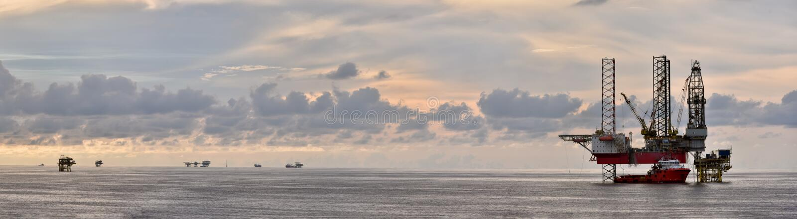 Oil rig platform at sea during sunset with beautiful cloud. Jack up rig and oil platform with supply vessel during sunset at sea with beautiful cloudy sky stock image