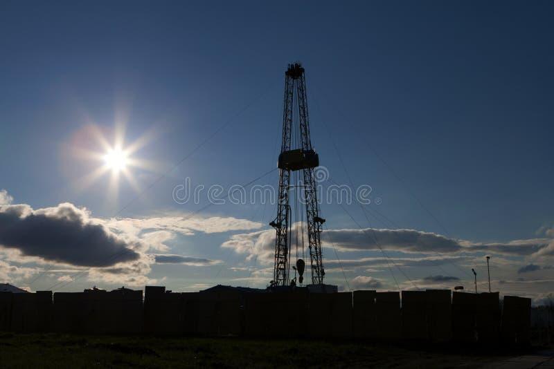 Oil rig silhouette, blue sky. stock photos