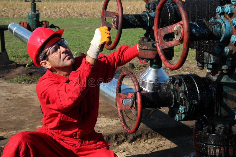 Oil Rig Worker. Oil worker turning valve on oil rig royalty free stock photo