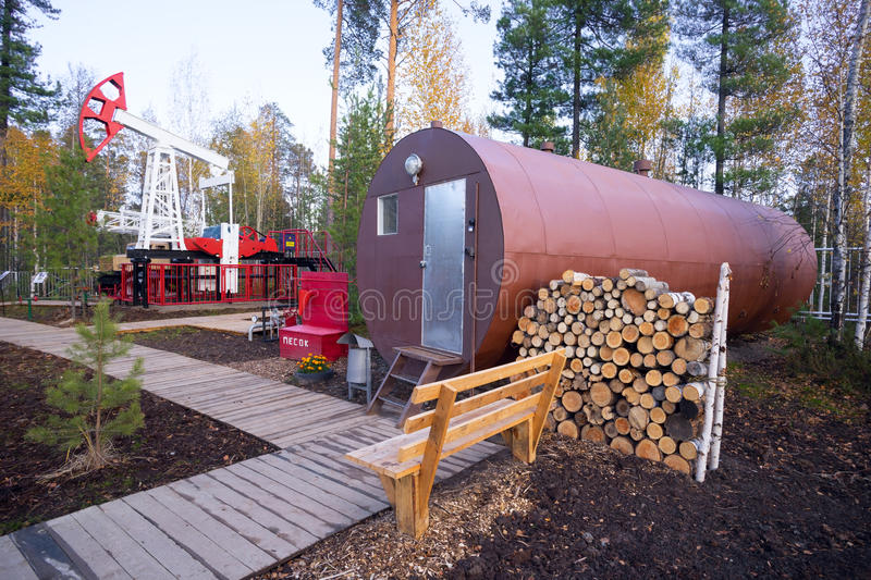 Oil rocking and residential trailer-a barrel with stock of firewood in the forest. stock photo