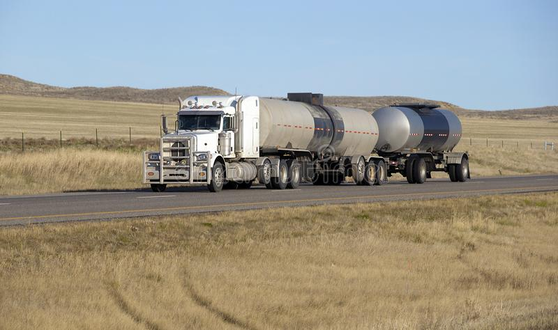 Oil transport semi truck. Oil semi truck with white trailer driving on highway royalty free stock photo