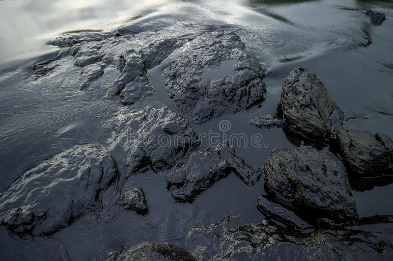 Oil sludge contaminating the sea during the oil spill disaster in Samet Island, Rayong, Thailand.  stock photos