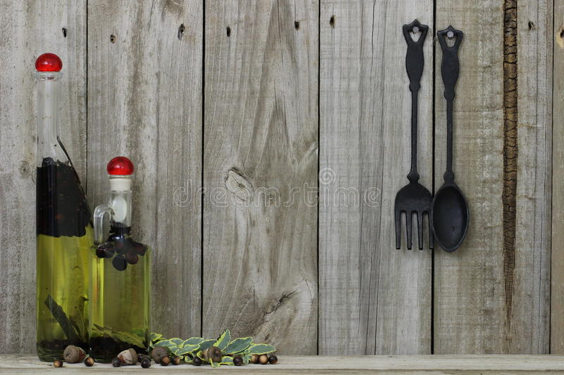 Oil spice jars with cast iron spoon and fork against wood background stock photo