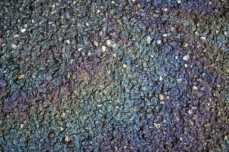 Oil spill on asphalt road, abstract background or texture foe web site or mobile devices stock photography