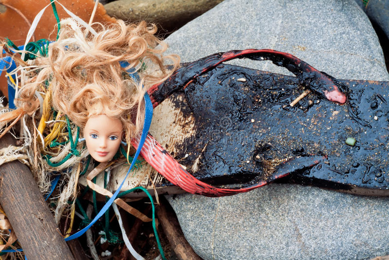 Oil spill flotsam washed ashore. Oil spill pollution hazard concept: blond doll head washed ashore next to ugly tar-covered beach flip-flop sandal stock images