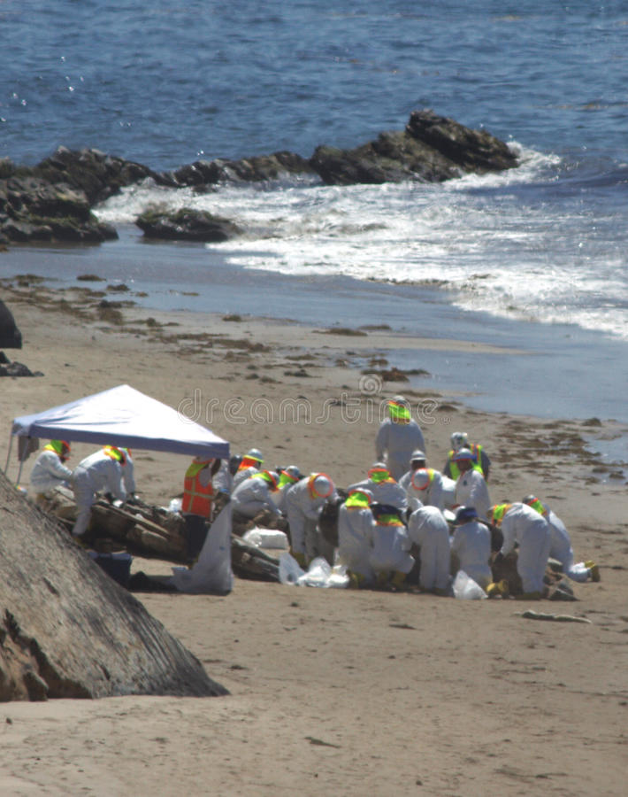 Oil Spill Hazmat Clean Up. Taken June 23, 2015 after the oil spill in Santa Barbara California. Hazmat suite workers focused in one area of beach stock image