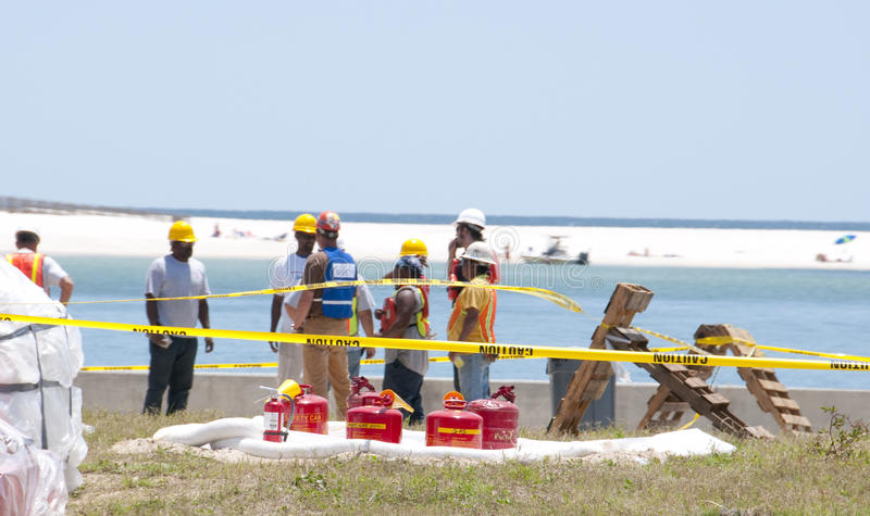 Oil spill workers at seashore. GULF SHORES - MAY 8: Workers gather on May 8, 2010 to protect beautiful Gulf Shores, Alabama from the BP oil spill that threatens royalty free stock images