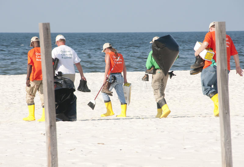 Oil spill workers at seashore. PERDIDO KEY, FL - JUNE 9: Oil spill workers collect tainted debris and dark oil patches along the beach as oil washes ashore on royalty free stock photography