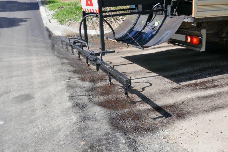 Oil spreader truck applying tack coats spraying bitumen emulsion with  spray lance before applying a new layer. Of asphalt stock image