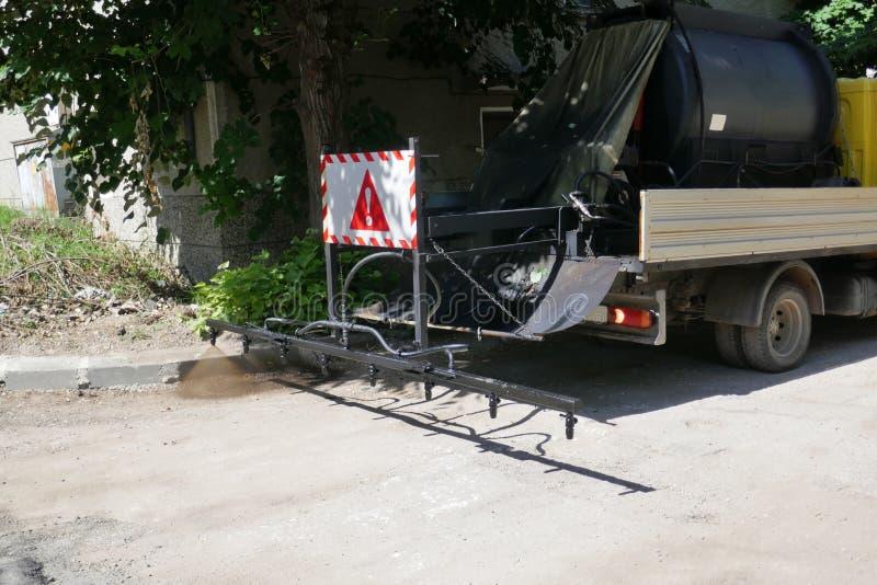 Oil spreader truck applying tack coats spraying bitumen emulsion with  spray lance before applying a new layer. Of asphalt stock photos